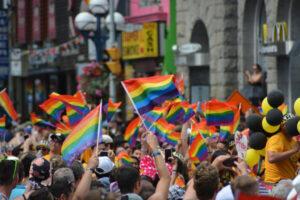 Crowd-waving-pride-flags-300×200